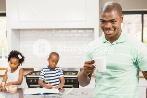 Father drinking hot beverage with children on background