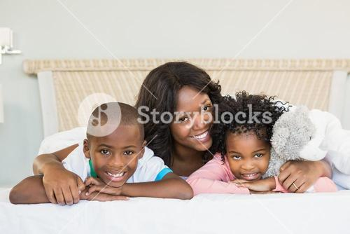 Mother and children lying on bed