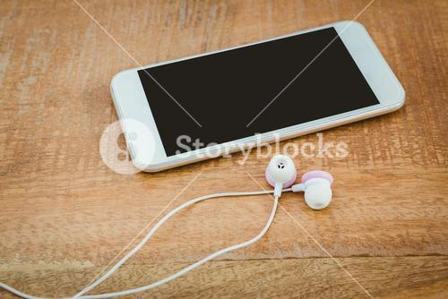White smartphone with white headphones