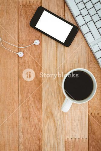 Black smartphone with cup of coffee