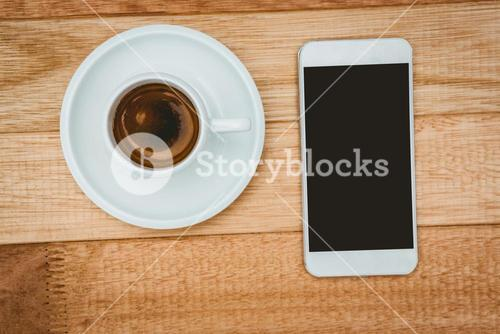 Above view of a coffee and a smartphone