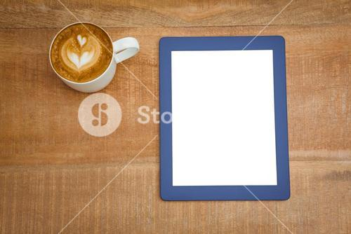 Above view of a coffee and a blue tablet