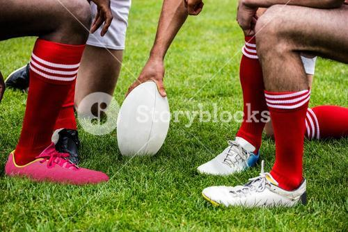 Rugby players in huddle with ball