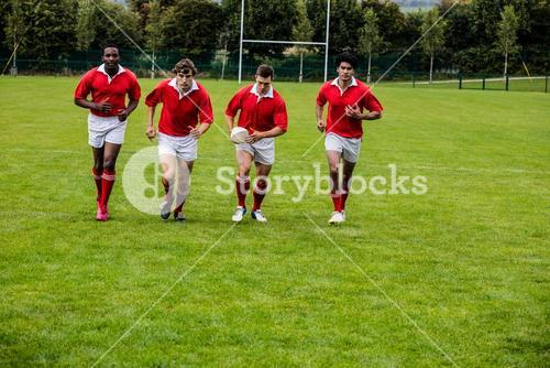 Rugby players jogging with ball