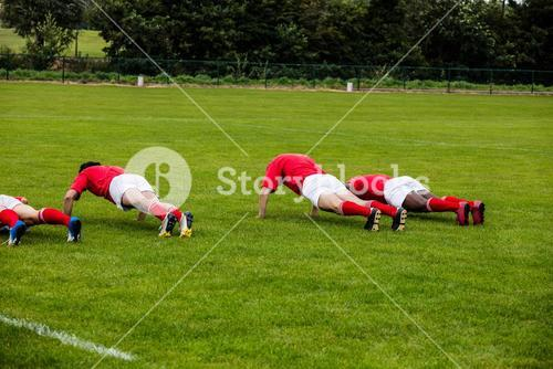 Rugby players doing push ups