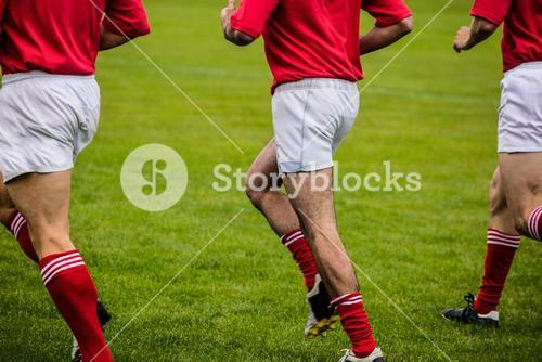 Rugby players jogging on pitch
