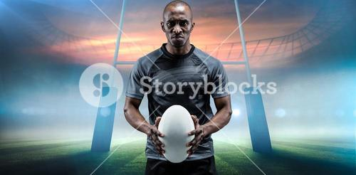 Composite image of portrait of serious athlete holding rugby ball