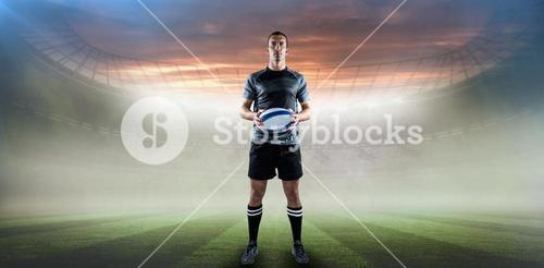 Composite image of serious rugby player in black jersey holding ball