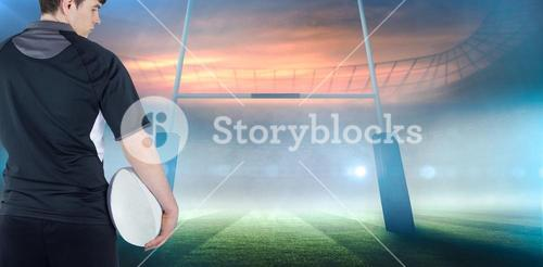 Composite image of back turned rugby player holding a ball