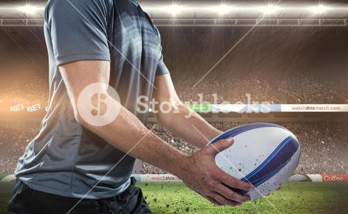Composite image of midsection of rugby player in black jersey holding ball