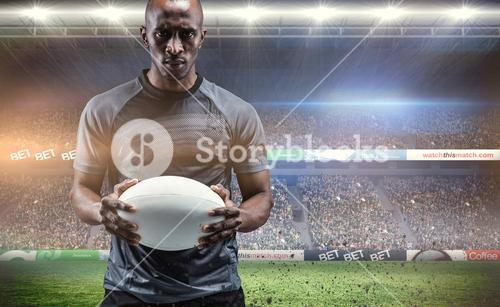 Composite image of portrait of serious sportsman holding rugby ball