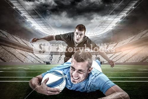 Composite image of confident rugby player lying in front with ball