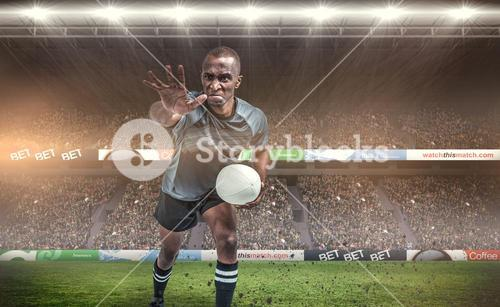 Composite image of aggressive rugby player gesturing while holding ball