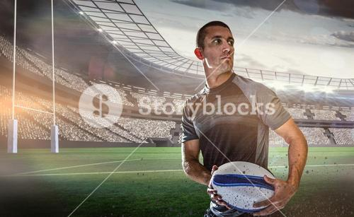 Composite image of sober rugby player holding ball