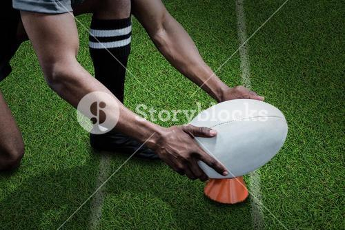 Composite image of cropped image of sportsman keeping rugby ball on kicking tee