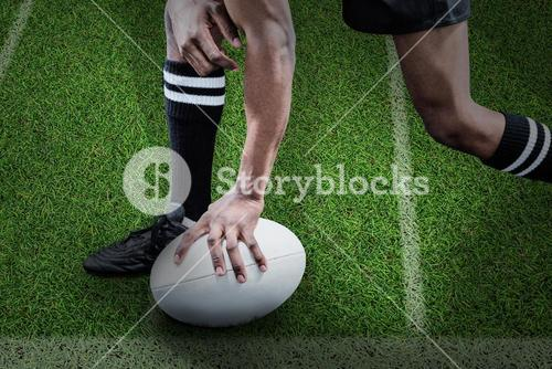 Composite image of low section of sportsman holding rugby ball