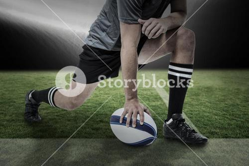Composite image of rugby player in black jersey stretching with ball