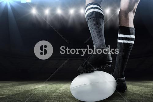Composite image of sportsman keeping leg on ball while playing rugby