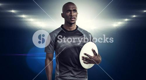 Composite image of thoughtful athlete holding rugby ball