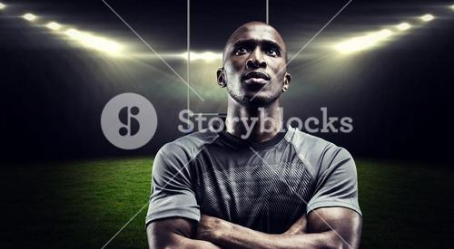 Composite image of thoughtful rugby player with arms crossed