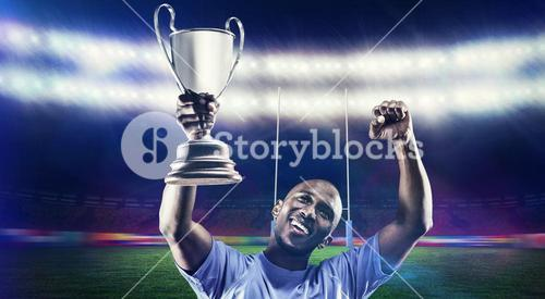Composite image of happy sportsman looking up and cheering while holding trophy