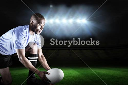 Composite image of rugby player looking away while keeping ball on kicking tee