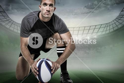 Composite image of portrait of rugby player in black jersey placing ball