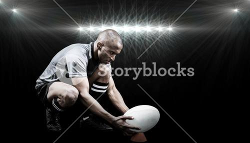 Composite image of rugby player keeping ball on kicking tee