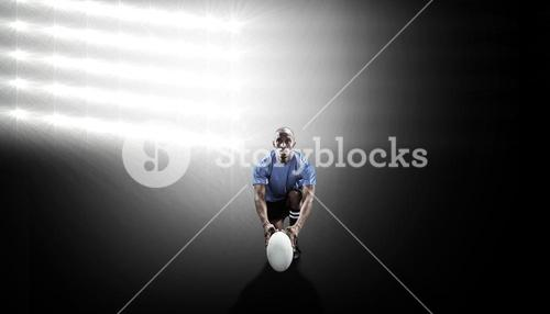 Composite image of portrait of rugby player holding ball while kneeling