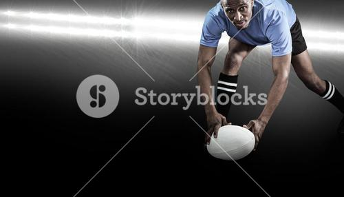 Composite image of portrait of sportsman bending and holding ball while playing rugby