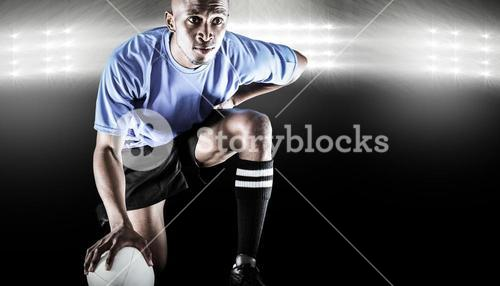 Composite image of serious rugby player kneeling while holding ball