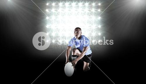 Composite image of rugby player holding ball while kneeling