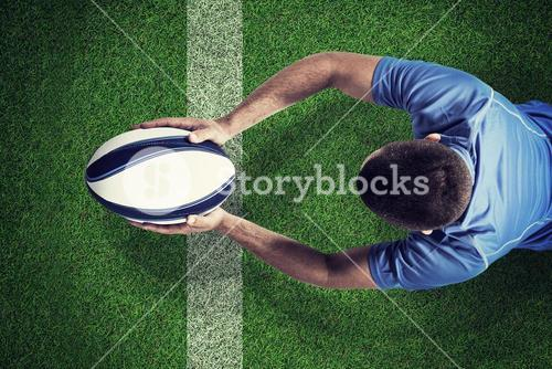Composite image of rugby player lying in front with ball
