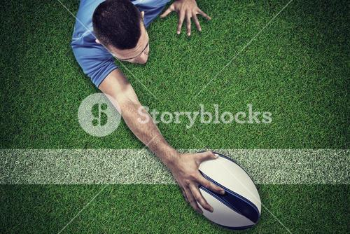Composite image of rear view of rugby player lying in front with ball