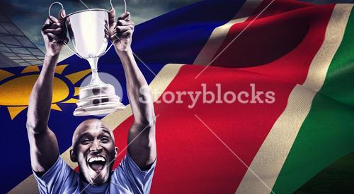 Composite image of happy athlete cheering while holding trophy