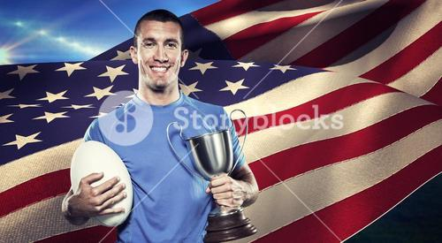 Composite image of portrait of smiling rugby player holding trophy and ball