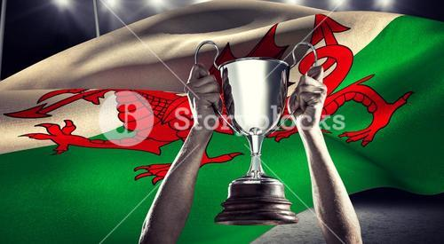 Composite image of successful rugby player holding trophy