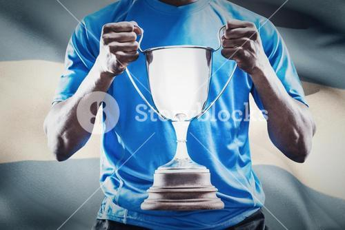 Composite image of mid section of sportsman holding trophy