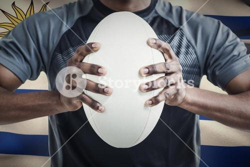 Composite image of cropped image of sportsman pressing rugby ball