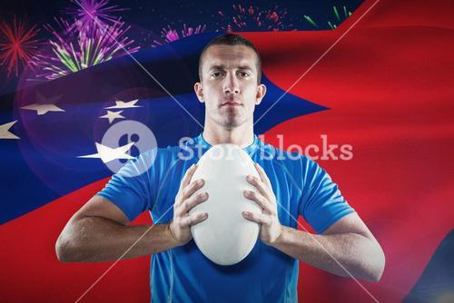 Composite image of portrait of confident sports player in blue jersey holding ball