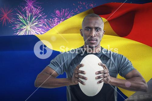Composite image of portrait of athlete pressing rugby ball