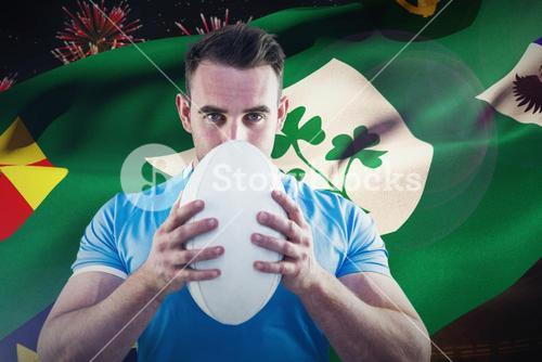 Composite image of rugby player looking at camera with ball