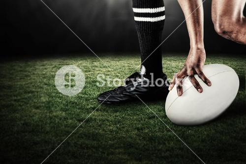 Composite image of low section of athlete holding ball while running