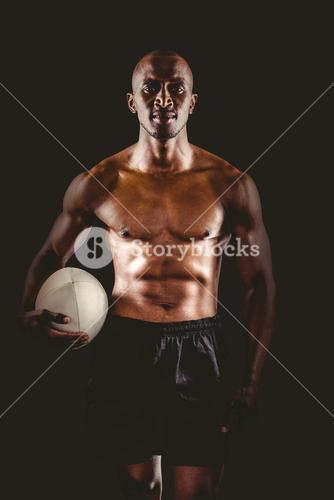 Portrait of shirtless sportsman holding rugby ball