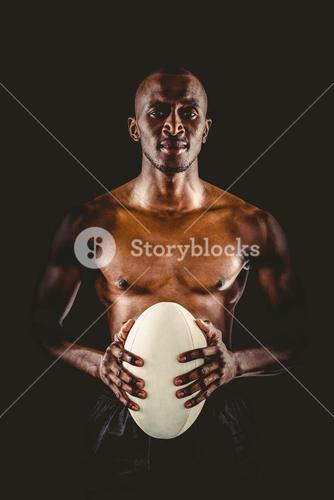 Portrait of shirtless athlete holding rugby ball