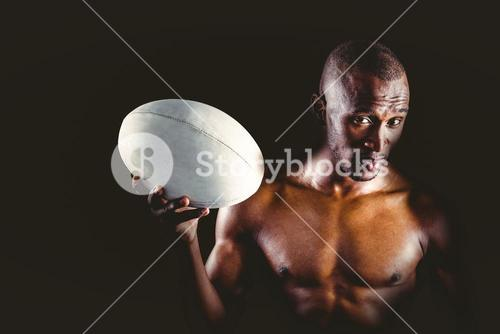 Portrait of confident shirtless sportsman holding rugby ball