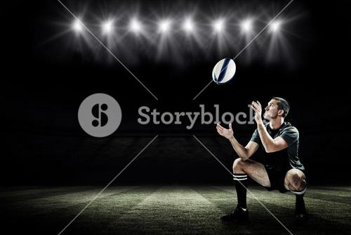 Composite image of full length of rugby player catching the ball