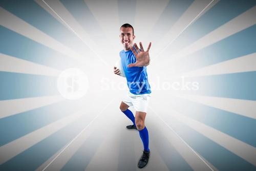 Composite image of full length portrait of happy rugby player defending