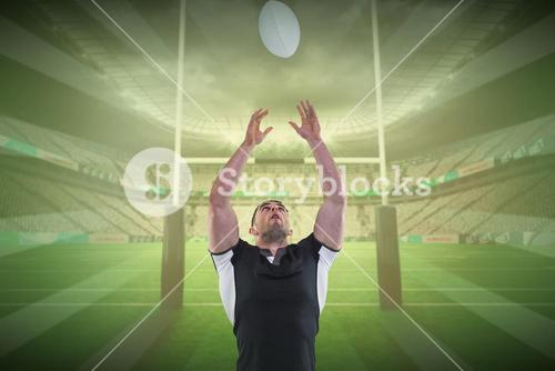 Composite image of rugby player catching the ball