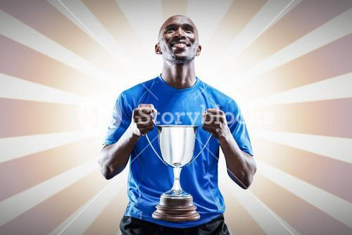 Composite image of happy athlete holding trophy looking up